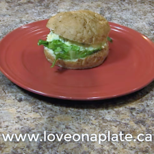 Egg Salad Sandwich with lettuce on a red plate.