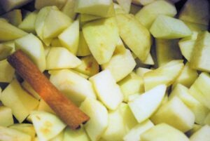 Close up of chopped apples and a cinnamon stick