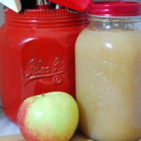 Apple Sauce in a mason jar, whole apple and red mason jar with cooking utensils