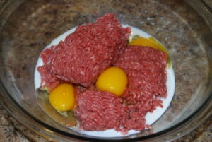 Ground Beef, Eggs, Milk in a glass bowl for prepping meatballs