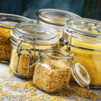 Assorted cereals and grains in glass jars for storage,
