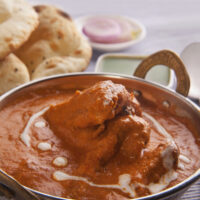 Butter Chicken in a dish with naan in the background