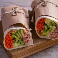Tuna wraps on wooden background. horizontal
