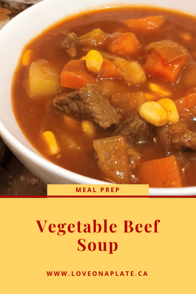 A white bowl with tomato beef broth with pieces of tender beef, corn, carrots and potatoes