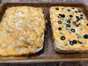 Foccacia Bread with Creamy Cheese Topping melted topped with chopped greem onion and sliced black olives