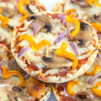 English Muffin with pizza sauce, melted cheese, sliced mushrooms and yellow peppers, close up