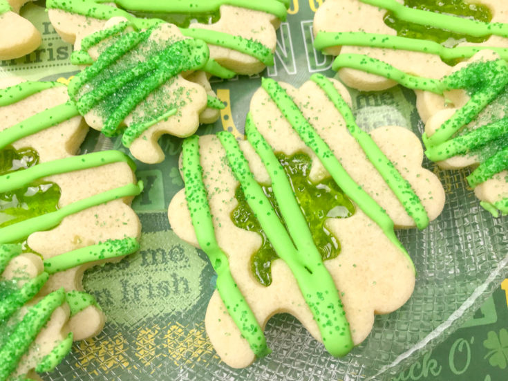 Close up of multiple Shamrock Sugar Cookies, with a green stained glass cut out, decorated with green icing and sprinkles