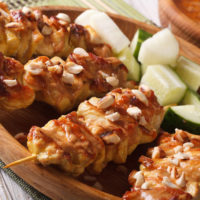 Chicken breasts on a skewer with peanut sauce and chopped peanuts on top on a wooden board