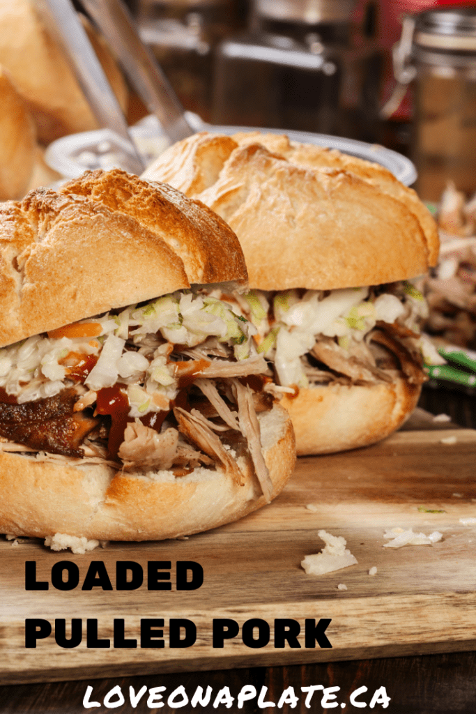 Closeup of two pulled pork sandwichses dressed with colewslaw and BBQ sauce on a wooden cutting board