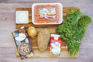soup ingredients laid out including ground sausage, onion, flour, broth, cream, kale, potato