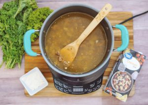 Browned ground sausage, onion, broth, and potato being simmered in a soup pot
