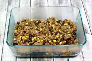Cooked ground turkey, black beans, corn, red onion in a glass 9X13 dish.