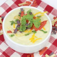 Cauliflower Hatch Green Chile soup in a ceramic white bowl on a red and white checked table cloth