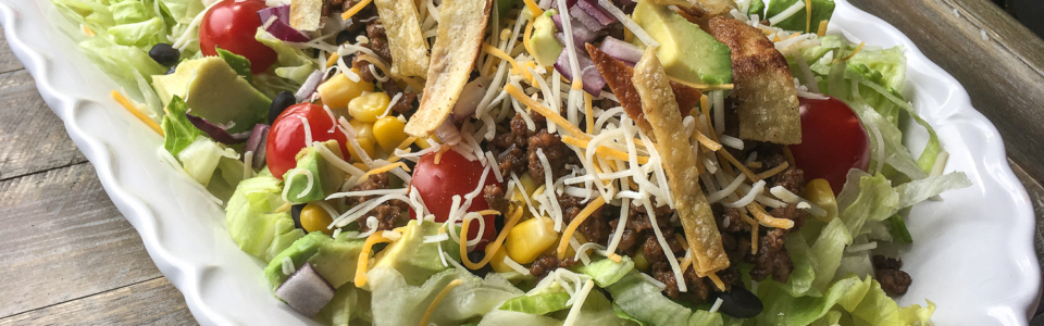 Large serving of beef taco salad on a white platter.