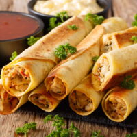 A stack of baked taquitos filled with chicken and cream cheese, piled on a wooden cutting board with a side dish of salsa