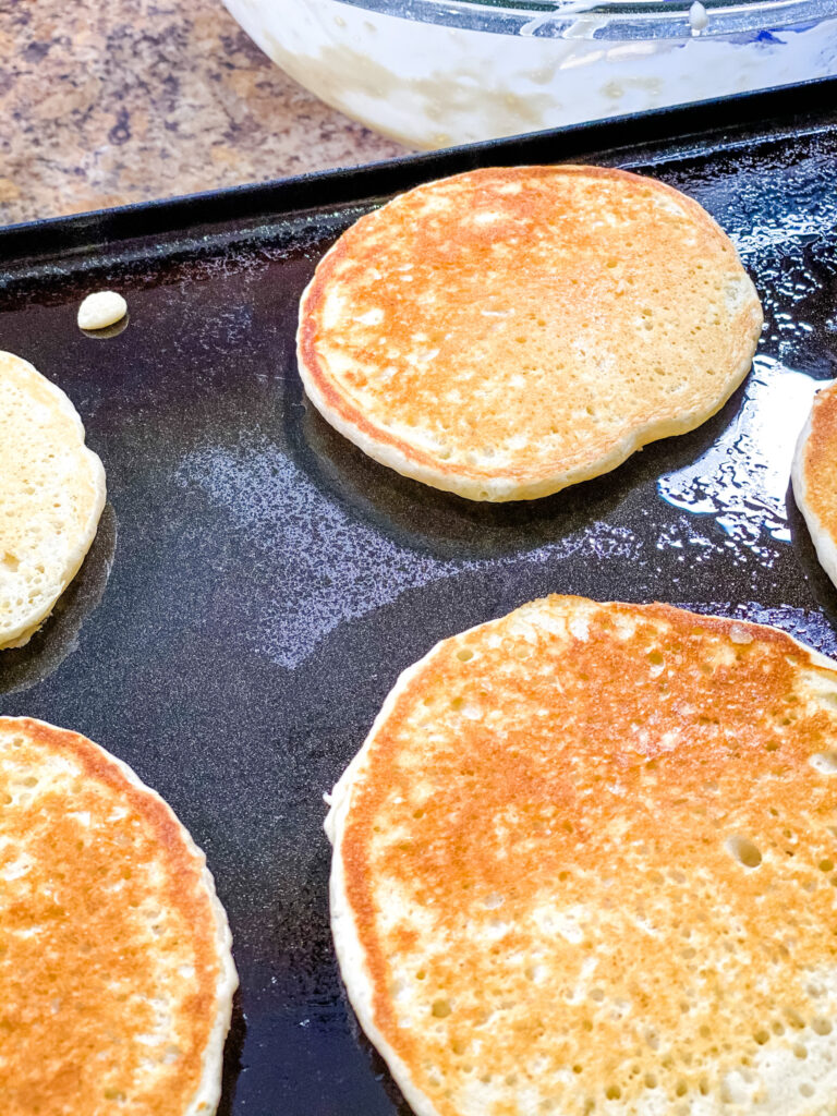 Golden brown sourdough pancakes cooking on a griddle