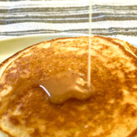 Closeup of 2 sourdough pancakes with syrup being drizzled on to them