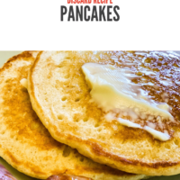 two sourdough pancakes topped with a pat of melting butter and syrup